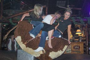Photo: 3 people riding mechanical bull